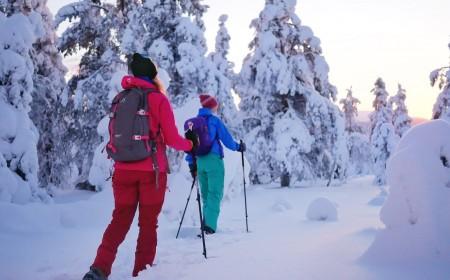 Kaksi ihmistä kulkee lumikengillä lumisessa metsässä.